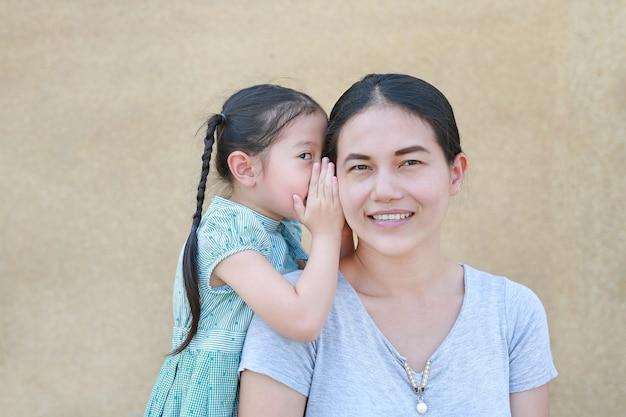 Piccola ragazza sveglia del bambino asiatico che bisbiglia un segreto al suo orecchio delle giovani madri a casa. Foto Premium