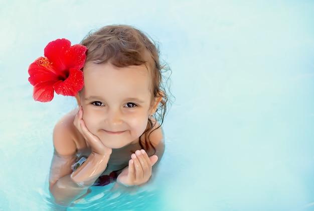 Piccola ragazza sveglia del bambino con il fiore rosso dietro il suo orecchio che si siede in un'acqua blu Foto Premium