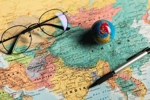 Piccola sfera del globo del mondo, occhiali e una penna sulla mappa. Foto Premium