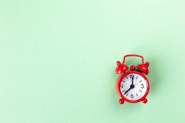 Piccola sveglia rossa su fondo verde pastello leggero Foto Premium