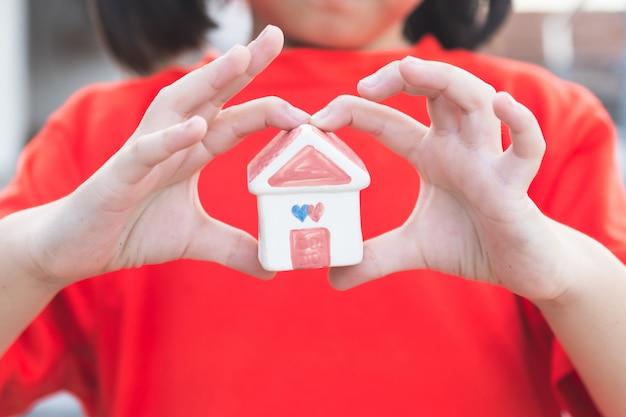 Piccole mani del bambino che tengono casa Foto Premium