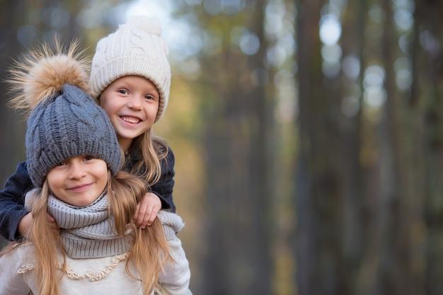 Piccole ragazze adorabili all'aperto al caldo soleggiato giorno d'autunno Foto Premium
