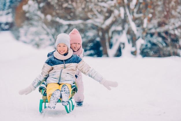 Piccole ragazze felici adorabili che sledding nel giorno nevoso di inverno. Foto Premium