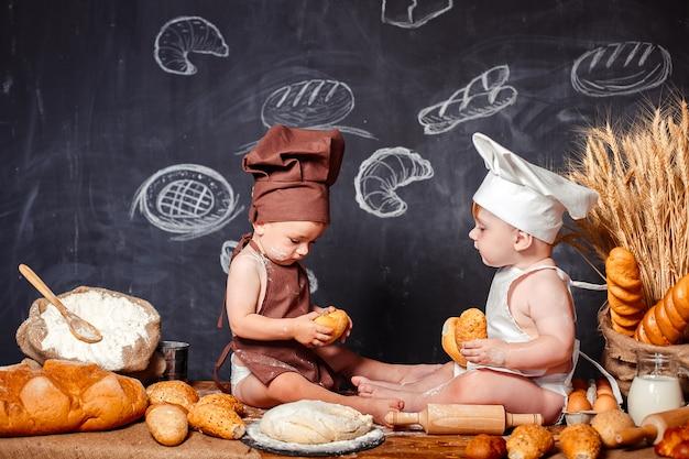 Piccoli bambini affascinanti in grembiuli sulla tavola con pane Foto Premium