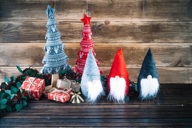 Piccoli elfi di natale con scatole regalo sul tavolo Foto Gratuite