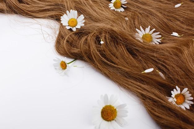 Piccoli fiori bianchi si trovano sui riccioli di capelli castani Foto Gratuite