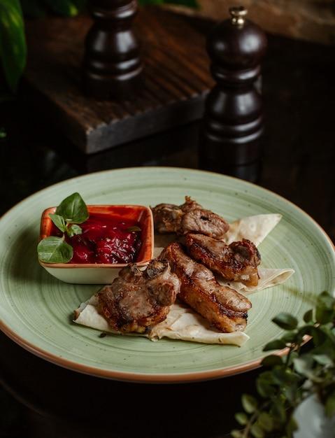 Piccoli pezzi di pollo grigliati e serviti con salsa di pomodoro e menta Foto Gratuite