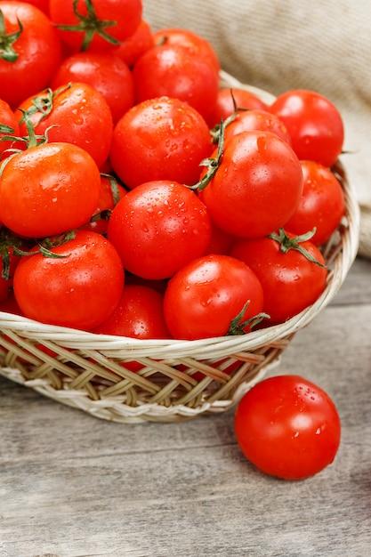 Piccoli pomodori rossi in un cestino di vimini su una vecchia tabella di legno. ciliegia matura e succosa Foto Premium