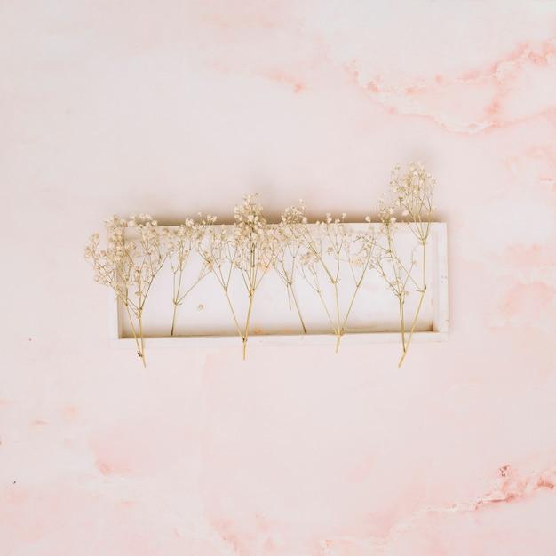 Piccoli rami di fiori sul bordo di legno sul tavolo Foto Gratuite