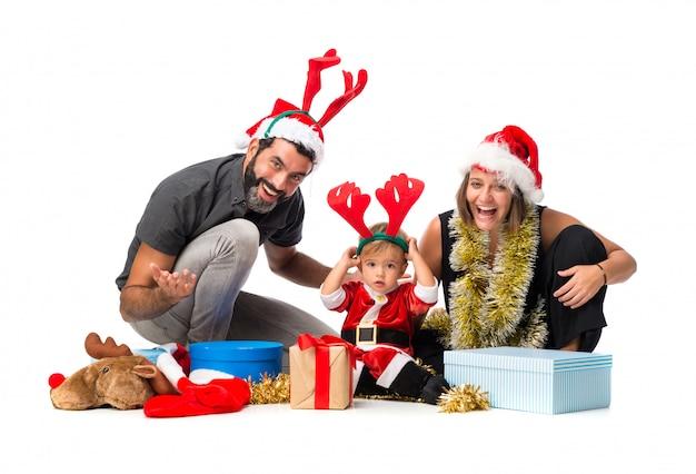 Piccolo bambino adorabile con i suoi genitori alle feste di natale su fondo bianco isolato Foto Premium