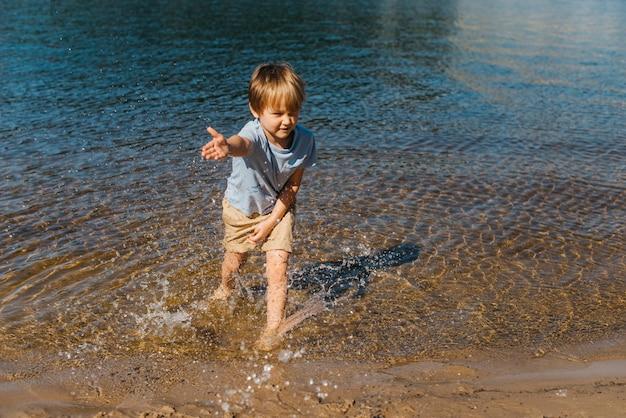 Piccolo bambino che spruzza acqua sulla spiaggia Foto Gratuite