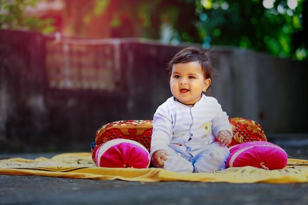 Piccolo bambino indiano sveglio che sorride e che gioca davanti alla casa Foto Premium