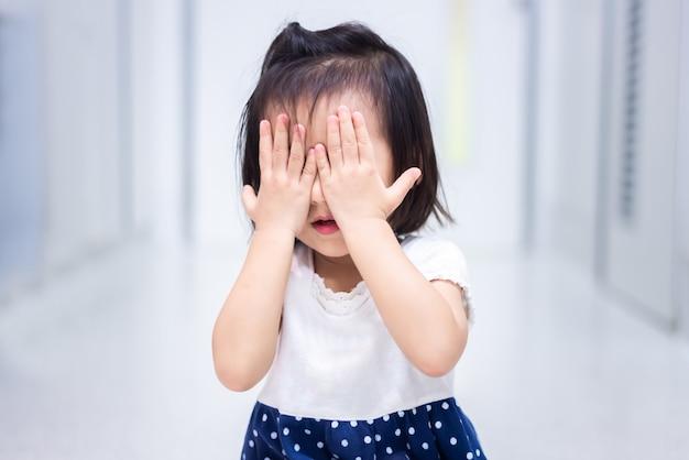 Piccolo bambino seduto su terra piangendo e coprirsi il viso con la mano Foto Premium