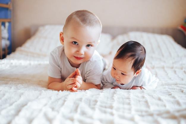 Piccolo bambino sveglio con il fratello maggiore che si trova sul letto a casa Foto Premium