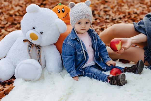 Piccolo bambino sveglio nel parco sulla foglia gialla con la zucca in autunno Foto Premium