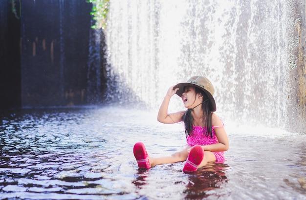 Piccolo cappello asiatico felice di usura della ragazza che gioca cascata in vacanza Foto Premium
