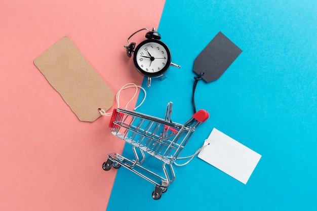 Piccolo carrello con sveglia. concetto di tempo di shopping Foto Premium