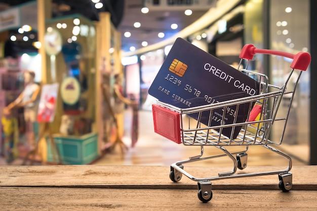 Piccolo carrello della spesa con carta di credito dentro e dietro è sfocato. shop - concept usa il credito per lo shopping. Foto Premium