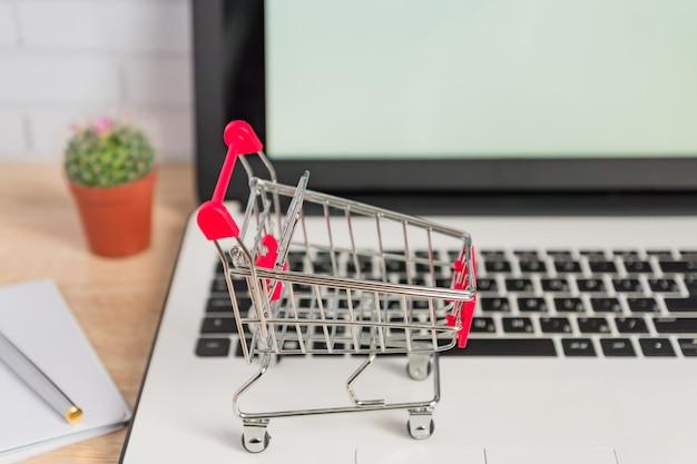 Piccolo carrello o carrello rosso sulla tastiera del computer portatile. concetto di shopping online di tecnologia business Foto Premium