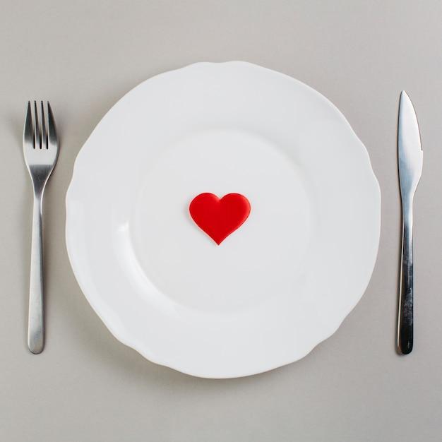 Piccolo cuore rosso sul piatto Foto Gratuite