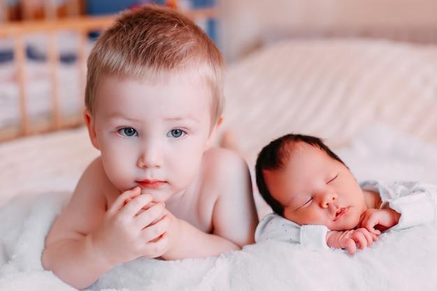Piccolo fratello del bambino che si trova vicino alla sorella del neonato, non è così felice a causa di esso Foto Premium