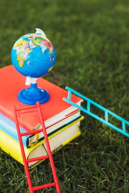 Piccolo globo disposto in cima alla pila di libri Foto Gratuite