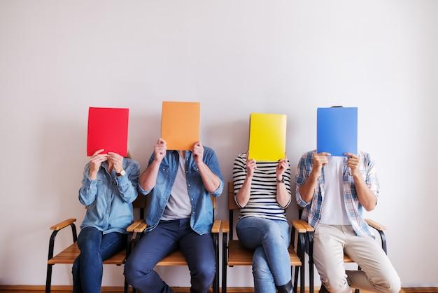 Piccolo gruppo di persone in possesso di cartelle davanti ai loro volti e seduti su sedie. sullo sfondo muro bianco. avviare il concetto di business. Foto Premium