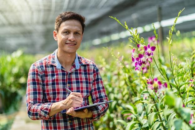 Piccolo imprenditore asiatico del ritratto dell'azienda agricola di giardinaggio dell'orchidea Foto Premium