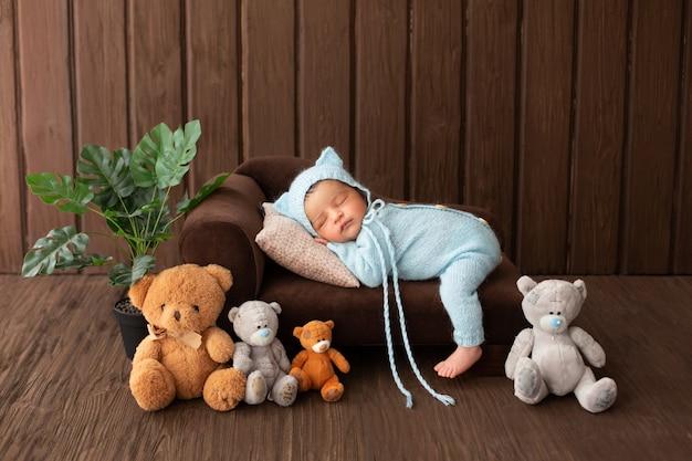 Piccolo neonato simpatico e grazioso del neonato che dorme sul piccolo sofà marrone in pigiama blu circondato dalla pianta e dagli orsi del giocattolo Foto Gratuite