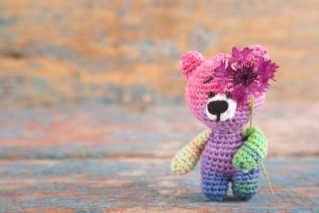 Piccolo orso a maglia multicolore con fiordalisi su un vecchio fondo di legno. Foto Premium