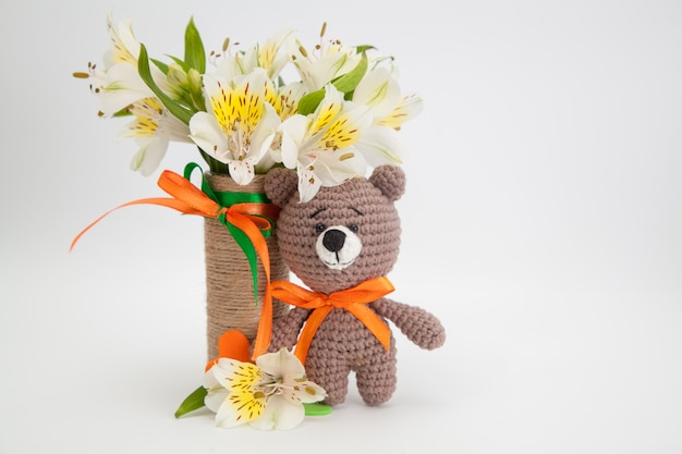 Piccolo orso bruno con fiori bianchi, giocattolo a maglia, fatto a mano. amigurumi. Foto Premium