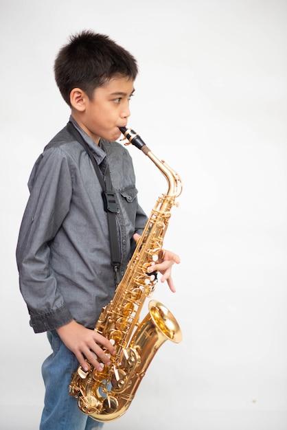 Piccolo ragazzo asiatico del musicista che gioca sassofono Foto Premium