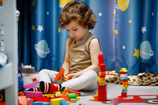 Piccolo ragazzo autistico che gioca con i cubi a casa Foto Premium