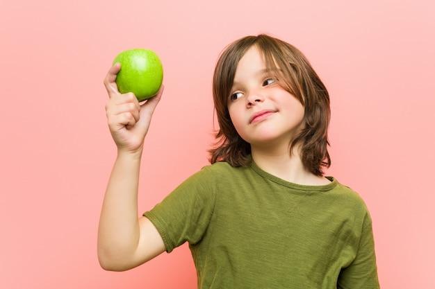 Piccolo ragazzo caucasico che tiene una mela Foto Premium