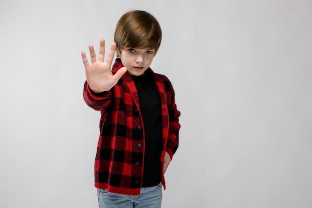 Piccolo ragazzo caucasico triste sicuro sicuro in fanale di arresto a quadretti di rappresentazione della camicia su gray Foto Premium