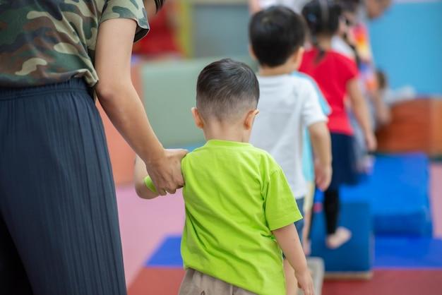 Piccolo ragazzo del bambino che risolve all'esercizio di ginnastica dell'interno Foto Premium