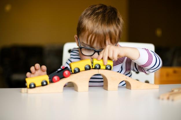 Piccolo ragazzo del bambino dello zenzero nei vetri con l'alba di sindrome che gioca con le ferrovie di legno Foto Premium