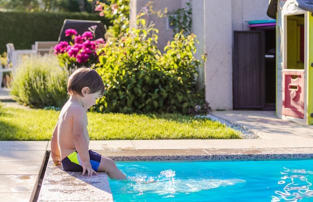 Piccolo ragazzo felice che si siede dal lato della piscina in giardino che gioca dai suoi piedi in acqua divertendosi. Foto Premium