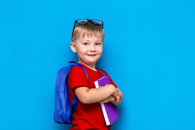 Piccolo ragazzo sorridente felice con gli occhiali sulla sua testa, libro in mano, zainetto sulle spalle. di nuovo a scuola. pronto a scuola Foto Premium