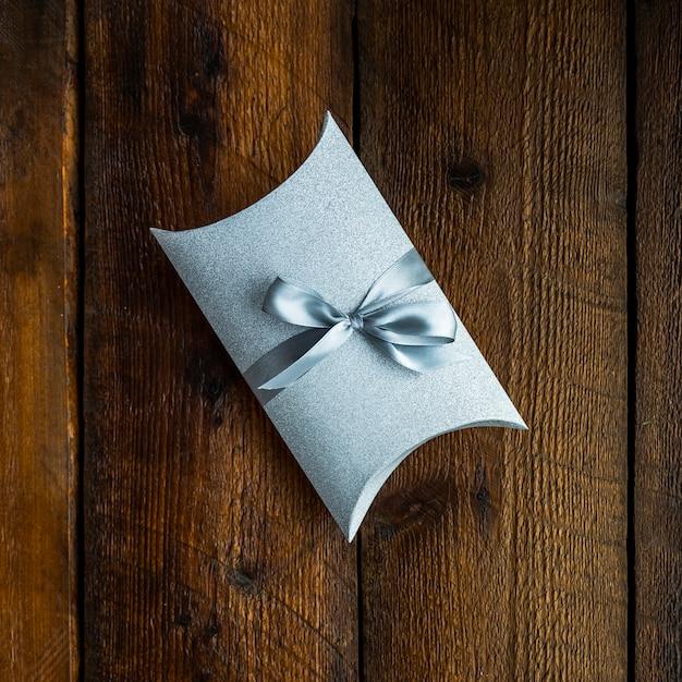 Piccolo regalo avvolto su fondo in legno Foto Gratuite