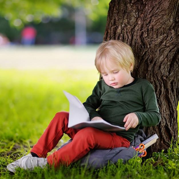 Piccolo scolaro sveglio che si siede sotto l'albero e lo studio. torna al concetto di scuola. Foto Premium