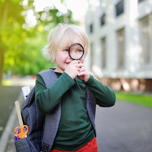 Piccolo scolaro sveglio con la lente d'ingrandimento che studia all'aperto il giorno soleggiato Foto Premium