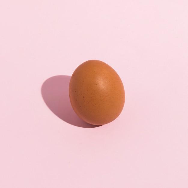 Piccolo uovo di gallina marrone sul tavolo rosa Foto Gratuite