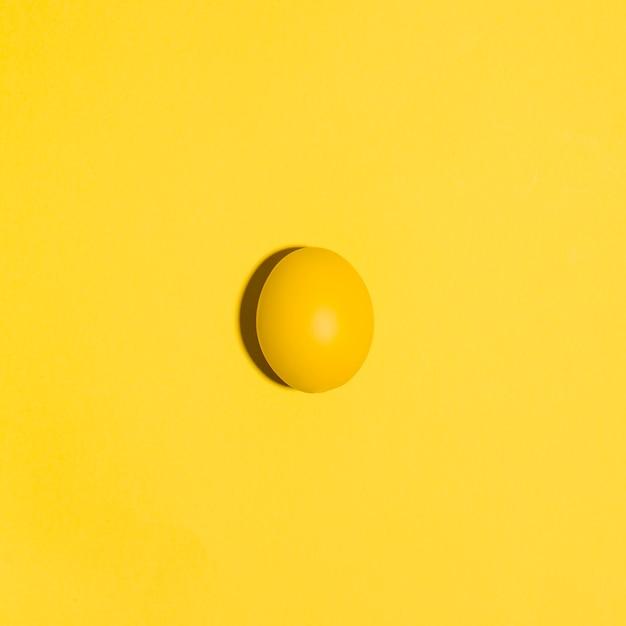 Piccolo uovo di pasqua giallo sul tavolo giallo Foto Gratuite