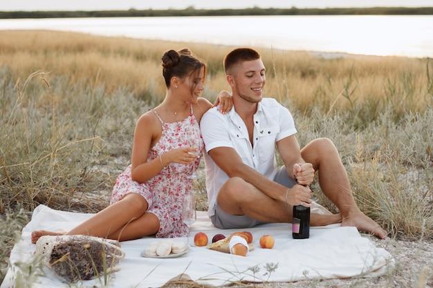 Picnic estivo in riva al mare. gli amanti delle coppie la sera mangiano frutta e bevono vino. serata romantica. proposta di matrimonio Foto Premium