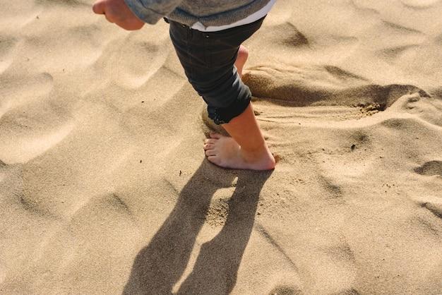 Piedi del ragazzo che cammina sulla sabbia della spiaggia. Foto Premium