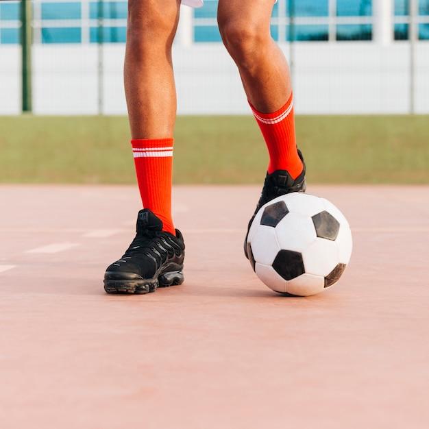 Piedi dello sportivo che giocano a calcio allo stadio Foto Gratuite