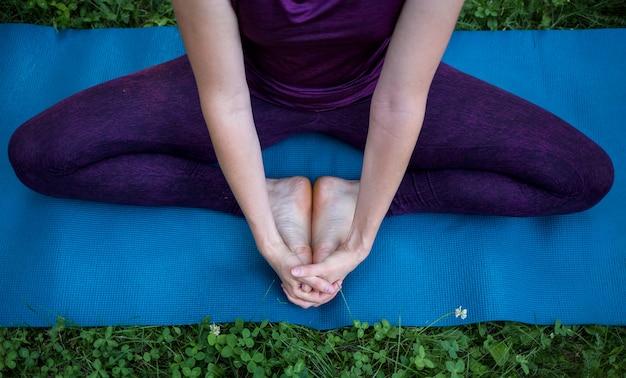 Piedi e mani di una ragazza seduta su un tappeto e meditando in natura Foto Premium