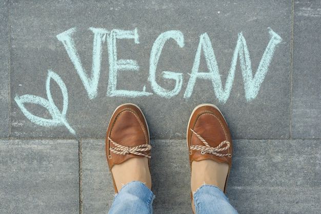 Piedi femminili con testo vegan scritto sul marciapiede grigio Foto Premium