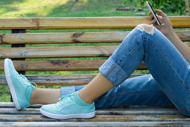 Piedi femminili in blue jeans e un primo piano disponibile del telefono cellulare Foto Premium